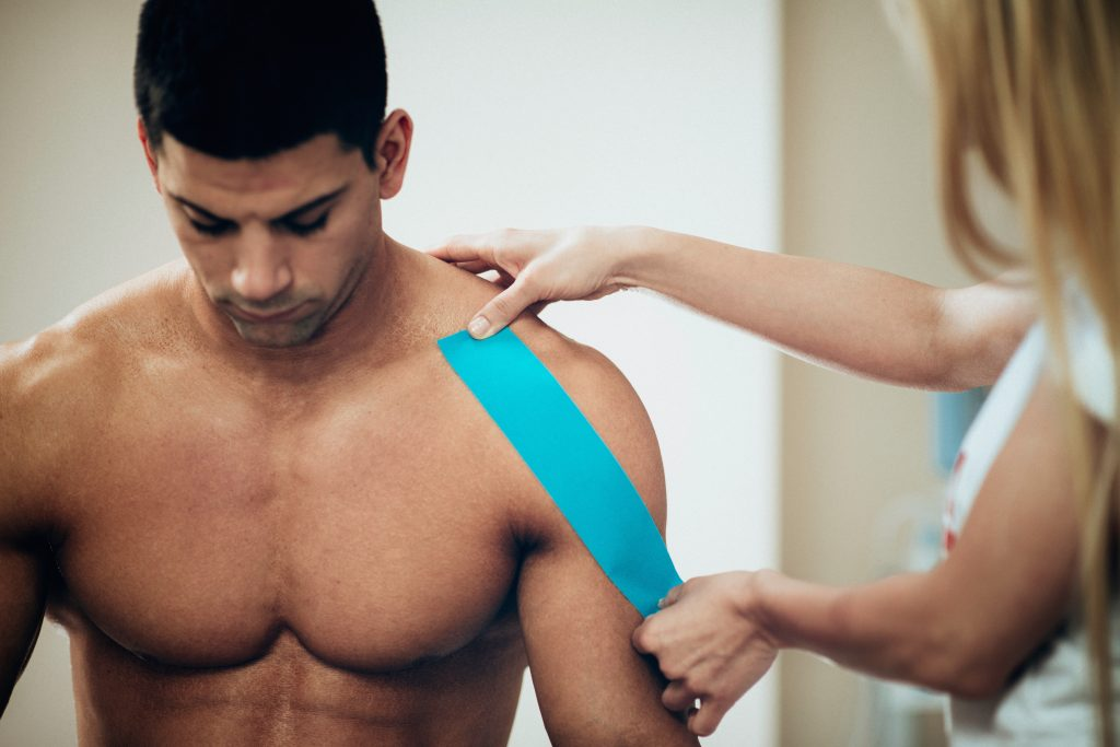 Practitioner is putting kinesiotape treatment onto the patient's